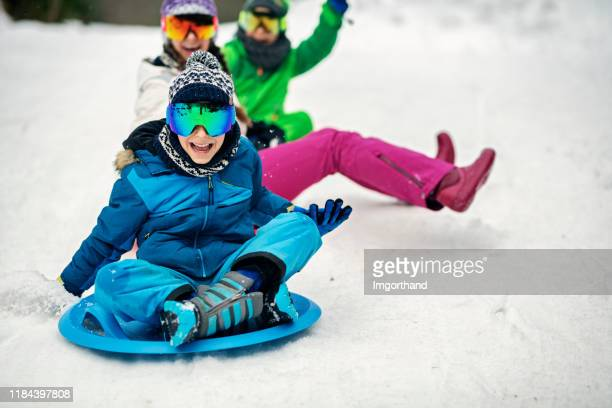 three kids sledding in winter. - tobogganing stock pictures, royalty-free photos & images