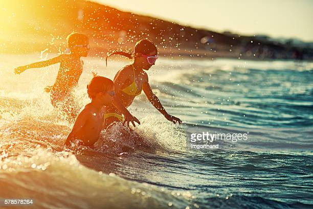Three kids swimming and having fun at sea at sunset