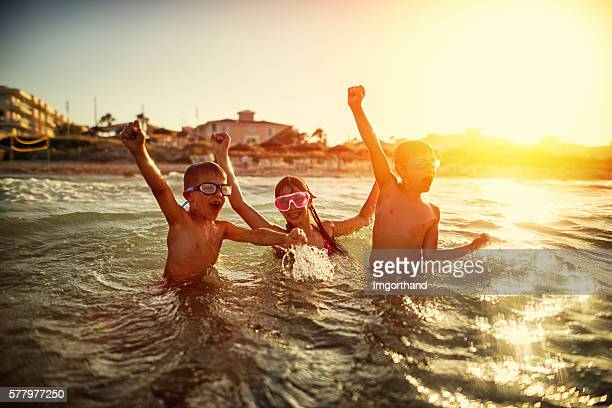 Three kids swimming and having fun in sea