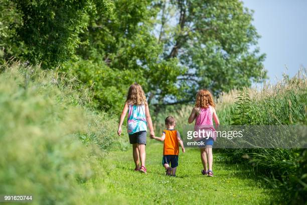 three kids walking down grass path on farm - lane sisters stock photos and pictures