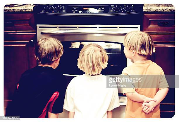 Three kids watching cookies bake