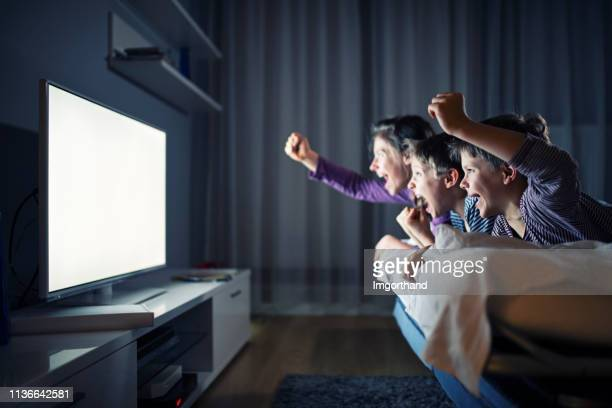 three kids watching tv and cheering - guardare con attenzione foto e immagini stock