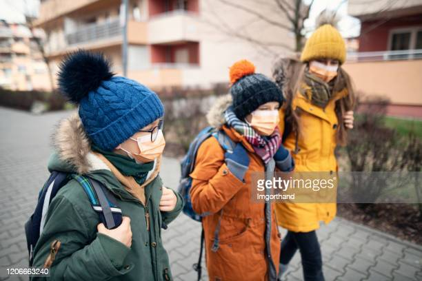 three kids wearing anti virus masks going to school - coronavirus stock pictures, royalty-free photos & images