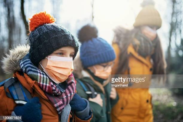 three kids wearing anti virus masks going to school - season stock pictures, royalty-free photos & images