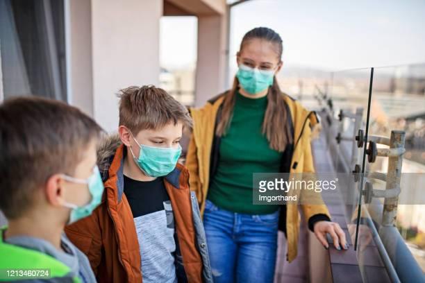 three kids wearing anti virus masks spending time on balcony - anti quarantine stock pictures, royalty-free photos & images