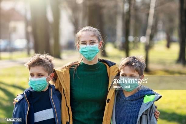 three kids wearing anti virus running in the park - mascherina antipolvere foto e immagini stock