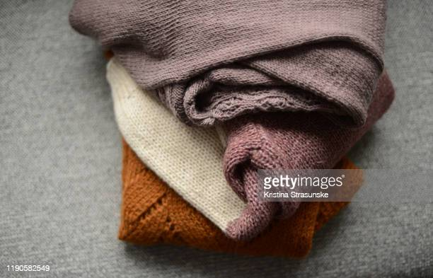 three knitted sweater on a sofa - cardigan sweater stock pictures, royalty-free photos & images