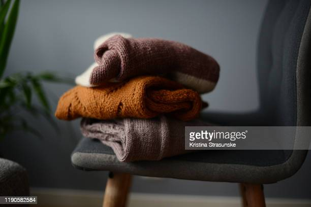 three knitted sweaters on a chair by a green plant - セーター ストックフォトと画像