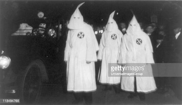 Three Ku Klux Klan members standing beside automobile driven by Klan members 1922 March
