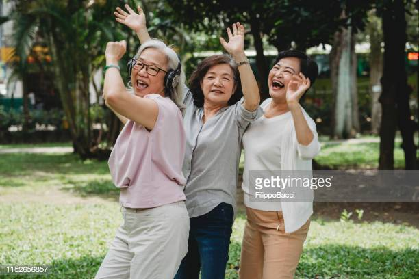 three ladies listening to music and dancing together at the park - chinese music stock pictures, royalty-free photos & images