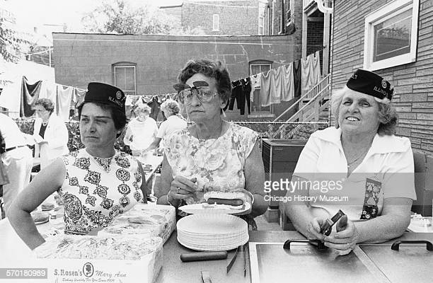 Three ladies serving hot dogs at a VFW post at Honore and Courtland Streets on Memorial Day Chicago Illinois May 30 1988