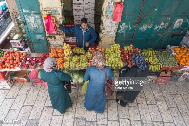 Three ladies shopping for fruit at a market stall next to Herod's Gate in the Old City on 31st March 2016 in Jerusalem West Bank