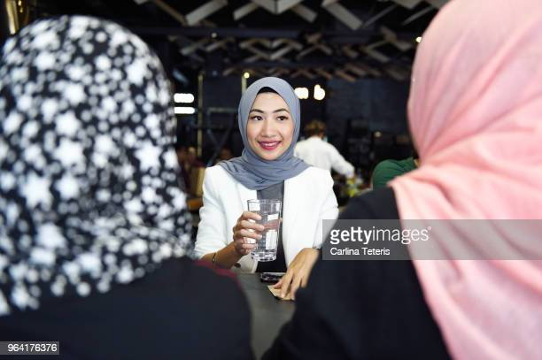 three ladies wearing headscarves chatting in a restaurant - expatriate stock pictures, royalty-free photos & images