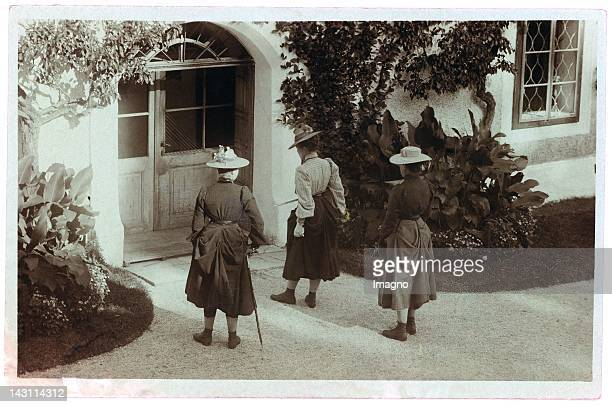 Three ladies wearing traditional hats and skirts that has been taken up for hiking in front of an entrance. Austria. Photograph. 1919.