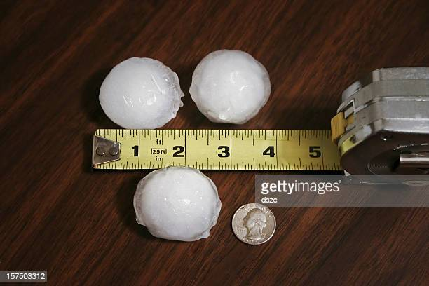 three large hailstones, tape measure, quarter