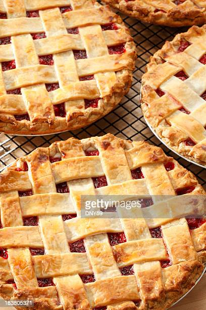 Three lattice topped cherry pies on a pie rack