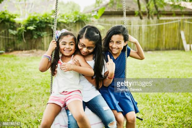Three laughing female cousins swinging on swing in backyard