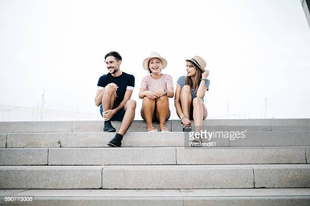 Three laughing friends sitting side by side on stairs