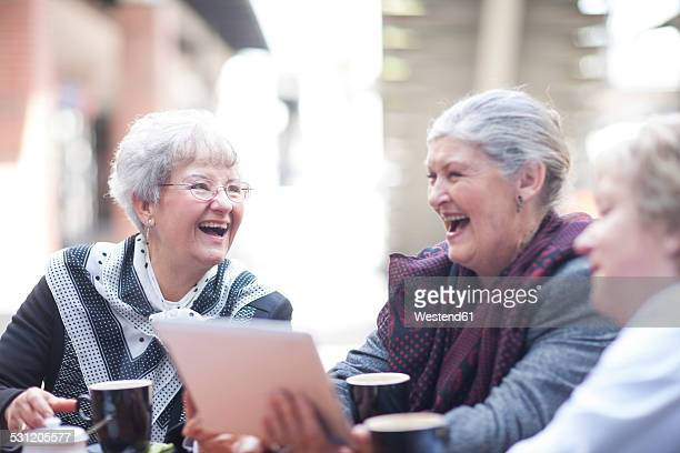 Three laughing senior women sitting in a pavement cafe