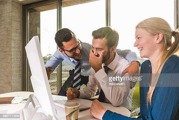 Three laughing young business people in conference room looking at monitor