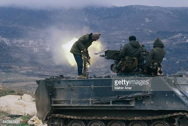 Three Lebanese fighters on top of a tank fire at the enemy in South Lebanon.