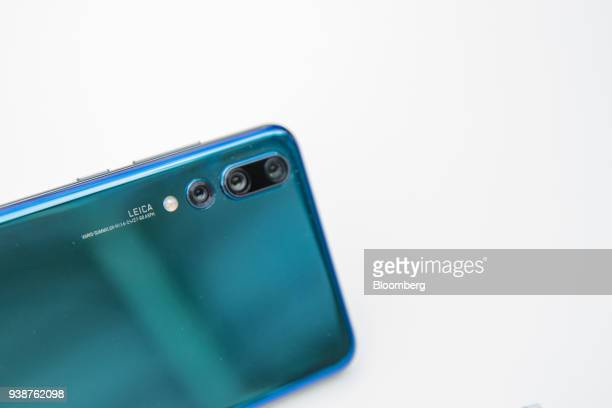 Three Leica Camera AG lenses sit on a P20 Pro smartphone manufactured by Huawei Technologies Co during its unveiling in Paris France on Tuesday March...