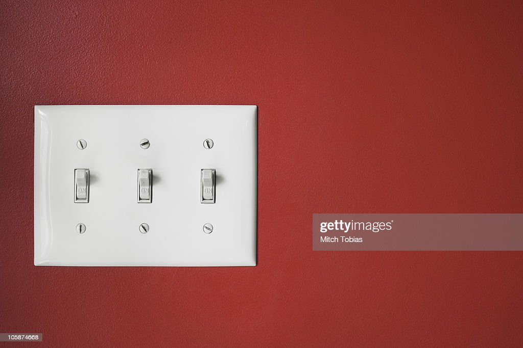 Three Light Switches On Red Wall Stock Photo | Getty Images