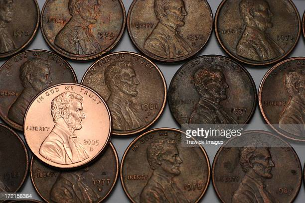 three lines of old pennies and one shiny new one - coin stock pictures, royalty-free photos & images