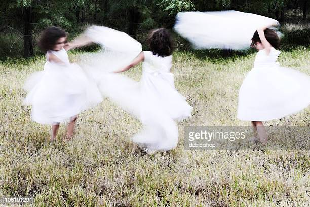 Three Little Girls Dancing In A Meadow
