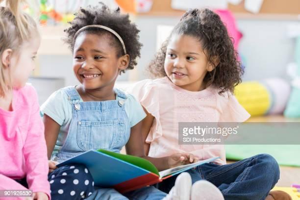 Drei kleine Mädchen diskutieren Buch zusammen in Kindergarten
