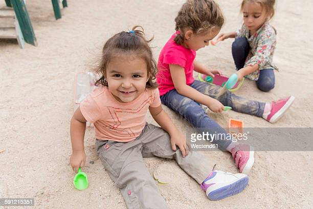 Three little girls playing in the sandbox of a playground