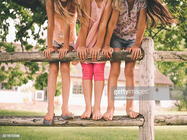 Three little girls standing on wooden fence in a park