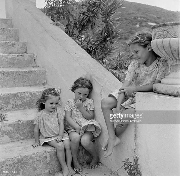 Three little local girls sit some steps in Charlotte Amalie St Thomas US Virgin Islands