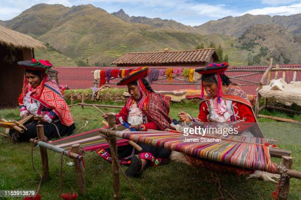 three local female weavers in colourful traditional local dress including festooned hats, weaving colourful alpaca wool on the ground, chumbe community, lamay, sacred valley, peru (3 model releases and property release) - peru stock pictures, royalty-free photos & images