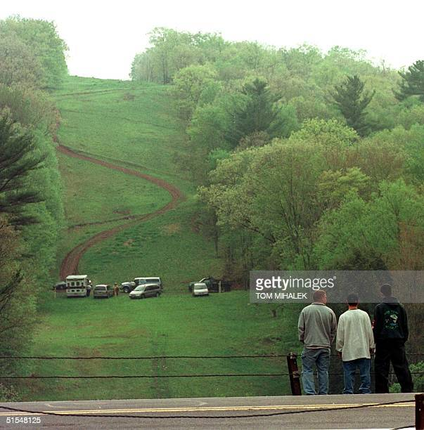 Three local men look towards emergency vehicles parked on a steep pipeline service road about one mile from the crash site of a commuter twin engine...