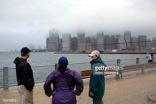 Three local residents stand in front of One Brooklyn Bridge Plaza apartments along the East River August 28 2011 in the Brooklyn borough of New York...