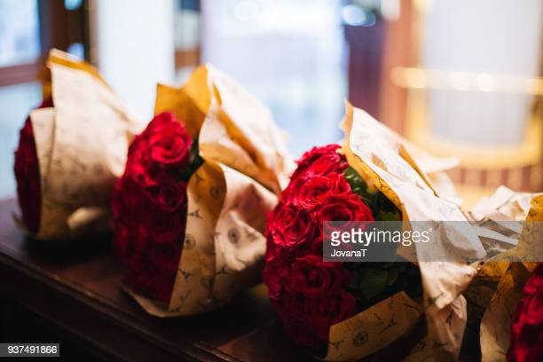 Three lovely red roses bouquets on table