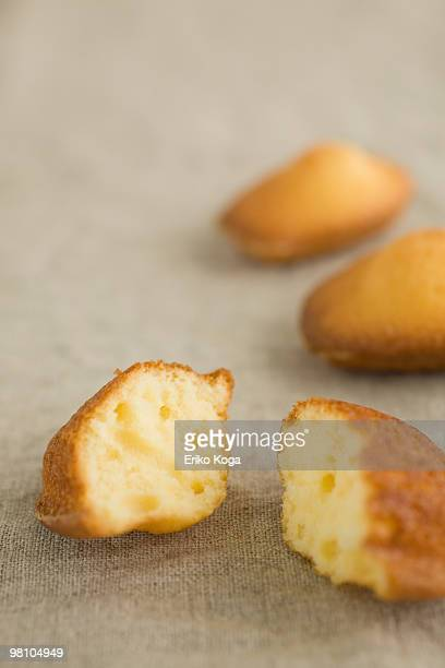 Three madeleines on cloth and one divided in two