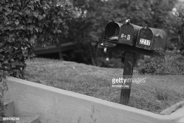 three mail boxes in front of a house - domestic mailbox stock pictures, royalty-free photos & images