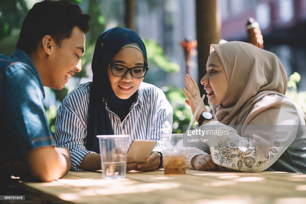 drei Malaiische Freunde sprechen, um andere zu erreichen, während der Suche in Smartphone : Stock-Foto
