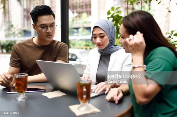 three malaysian colleagues having a business meeting outdoors - zurückhaltende kleidung stock-fotos und bilder