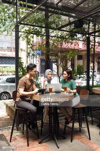 three malaysian colleagues having a business meeting outdoors - vestimenta religiosa - fotografias e filmes do acervo