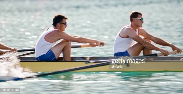 Three male athletes rowing across lake in late afternoon