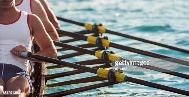 three male athletes rowing across lake in late afternoon - team sport stock pictures, royalty-free photos & images
