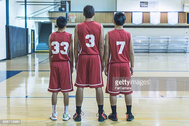 Three male basketball players waiting for a game to start