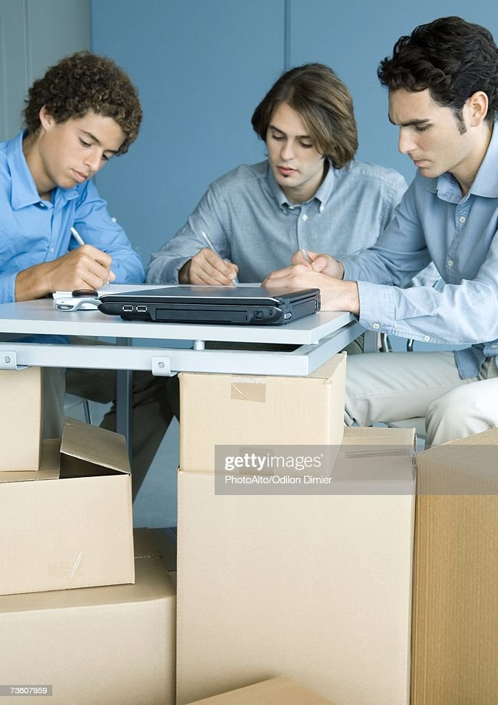 Three male colleagues working at table, cardboard boxes in foreground : Stock Photo