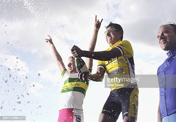 Three male cyclist standing on winner's podium, one opening champagne