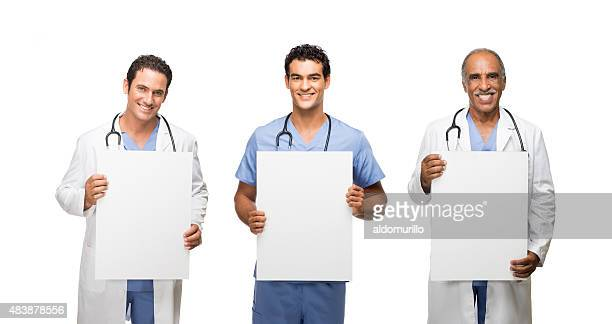 three male doctors holding placards - nursing slogans stock photos and pictures