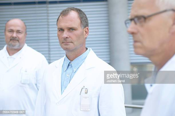 Three male doctors outdoors, focus on one in centre, portrait