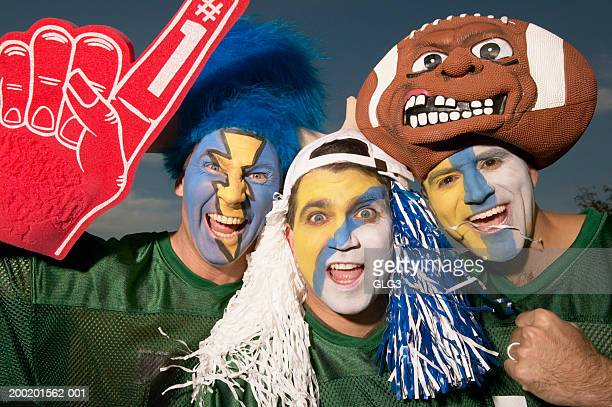 Three male football fans wearing face paint, gesturing